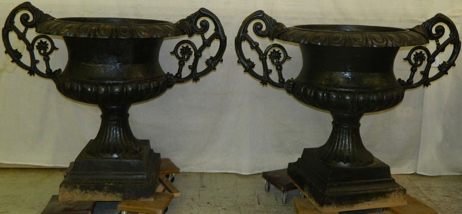 Pair of 19th Century cast iron urns on pedestals.