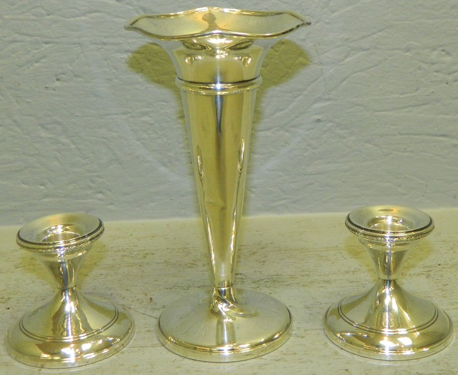 Sterling weighted vase and a pair of candlesticks.