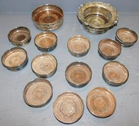 14 assorted silver plate wine coasters.