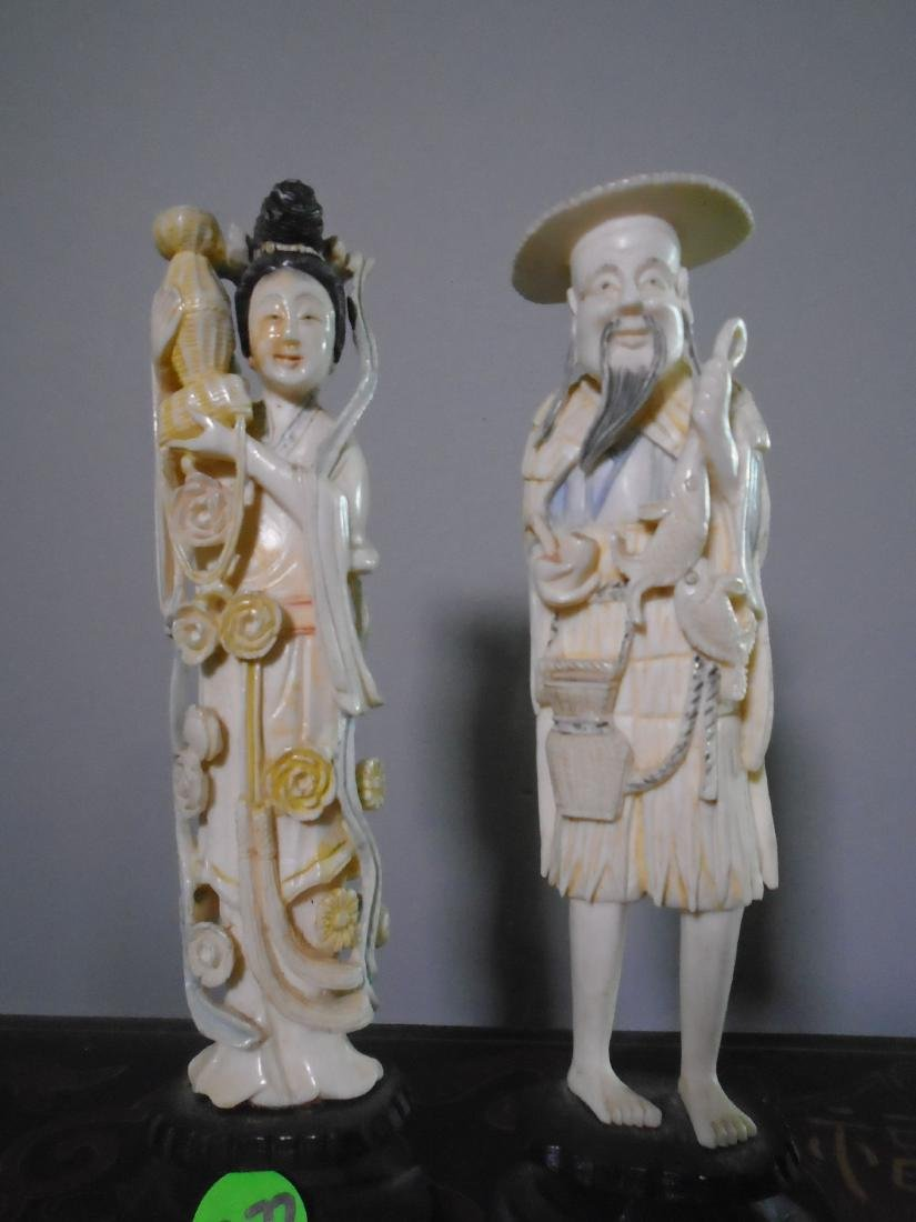 Pair of Hand carved bone oriental figurines on a wood