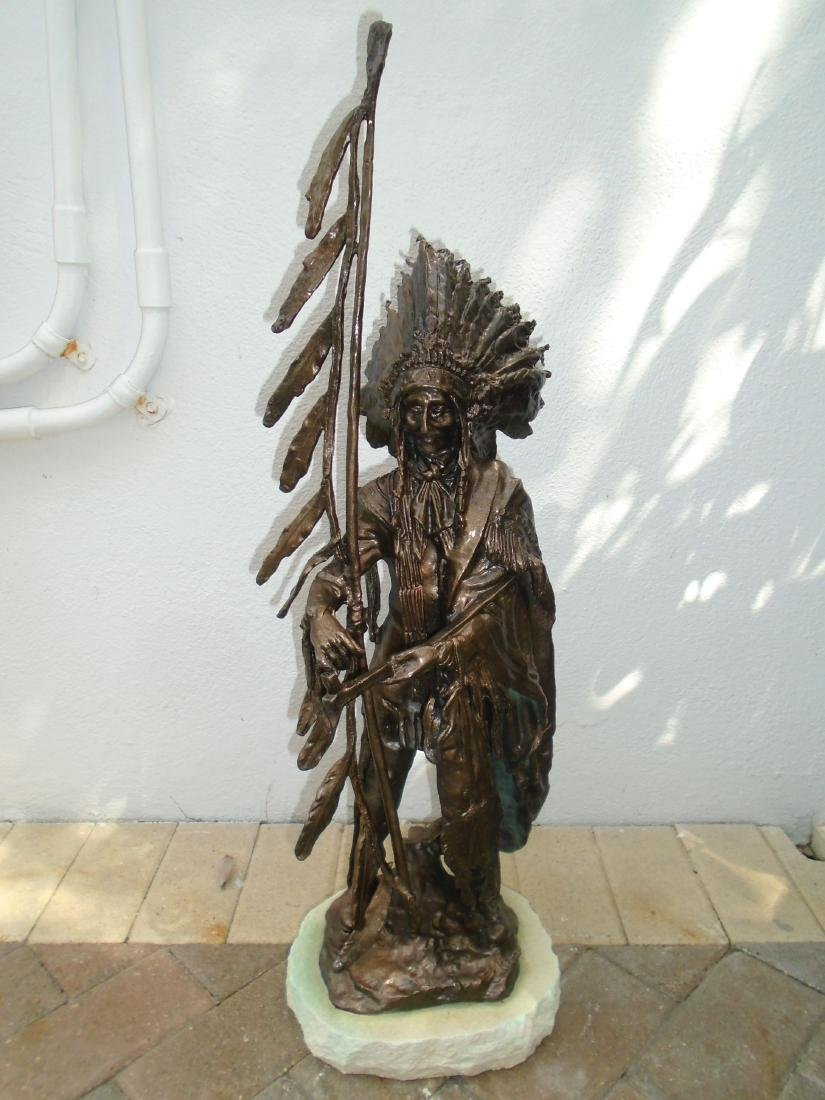 Indian chief standing holding a peace pipe & feathered