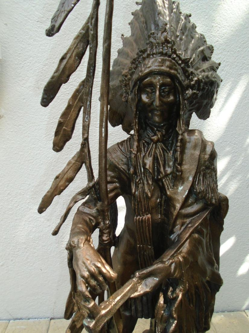 Indian chief standing holding a peace pipe & feathered - 2