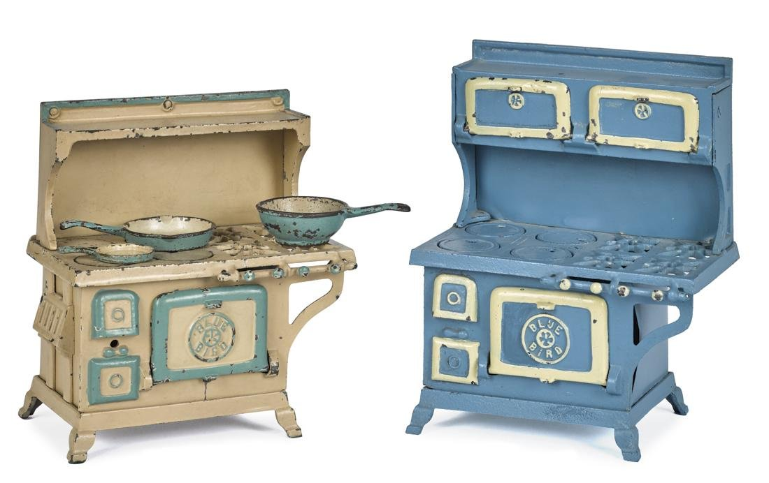 Two Grey Iron Blue Bird cast iron stoves, one with