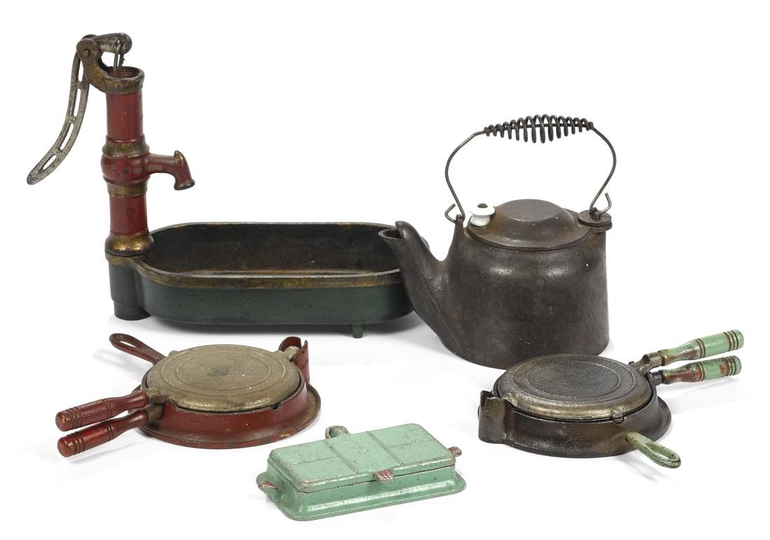 Four Arcade cast iron toys, to include a water pump and