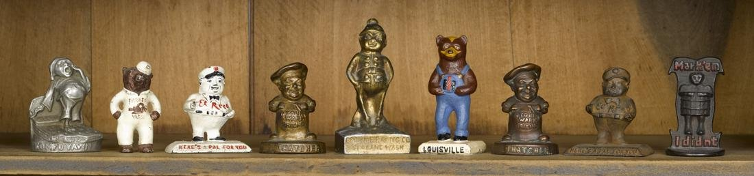Nine cast iron figural advertising paperweights, to