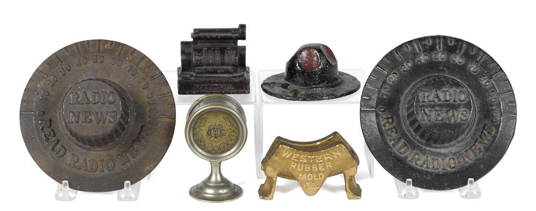Six cast iron news and advertising paperweights, to