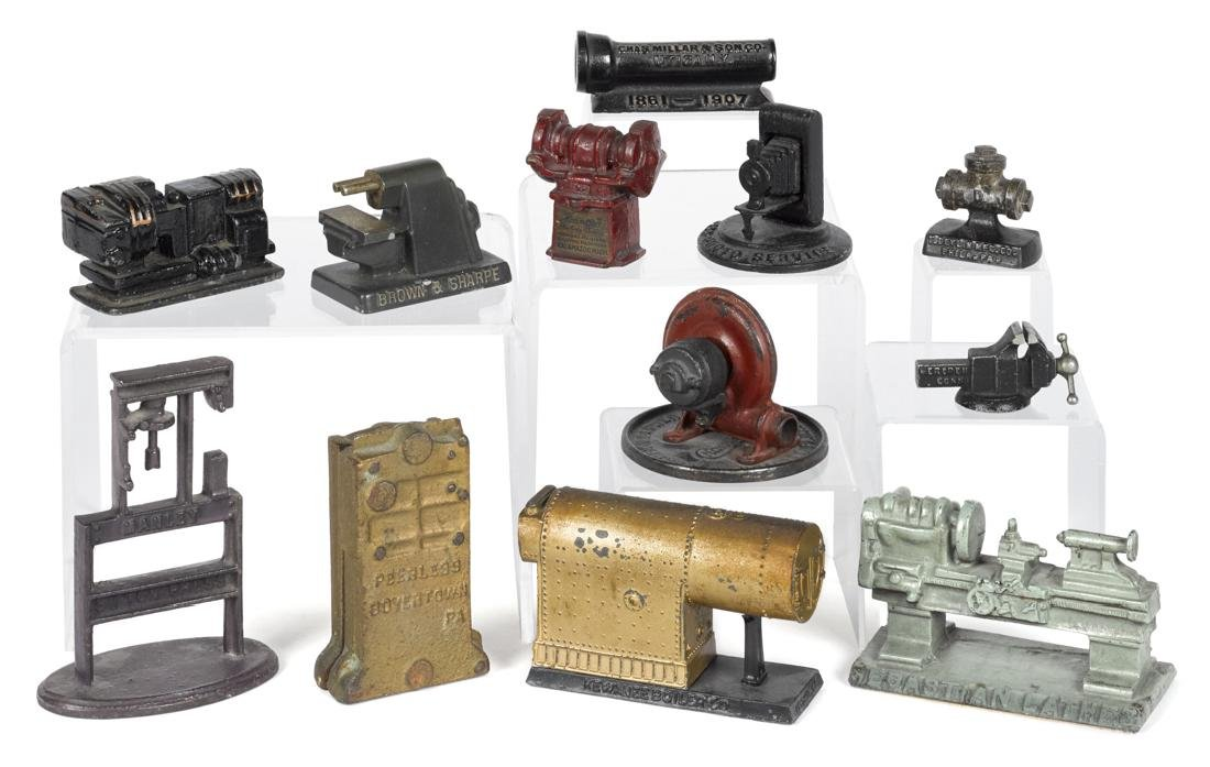 Twelve cast iron advertising paperweights and