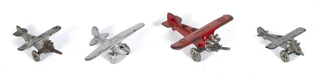 Four small cast iron airplanes, to include Lucky Boy,