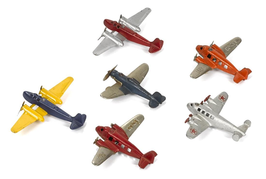 Six small cast iron airplanes, to include two TAT