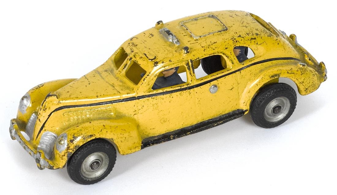 Arcade cast iron yellow cab with a painted driver and a