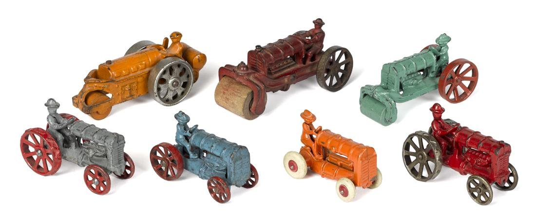 Seven small cast iron tractors and road rollers,