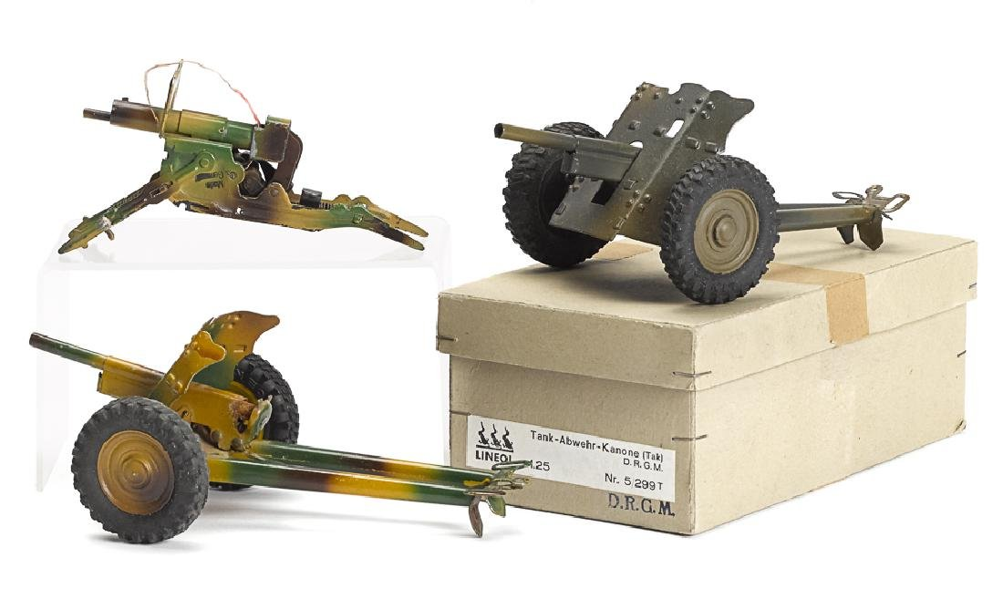 Three Lineol camouflage painted tin field guns