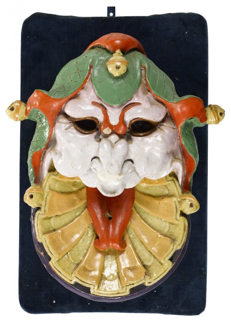 Grotesque clown face gargoyle, painted terra co