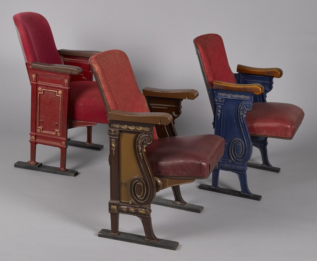 Three theater seats with ornate sides and scrol