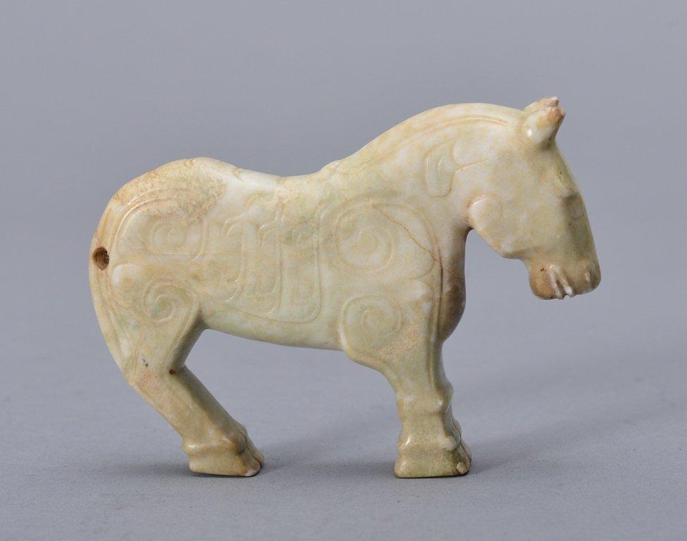A SMALL JADE SCULPTURE OF A STANDING HORSE