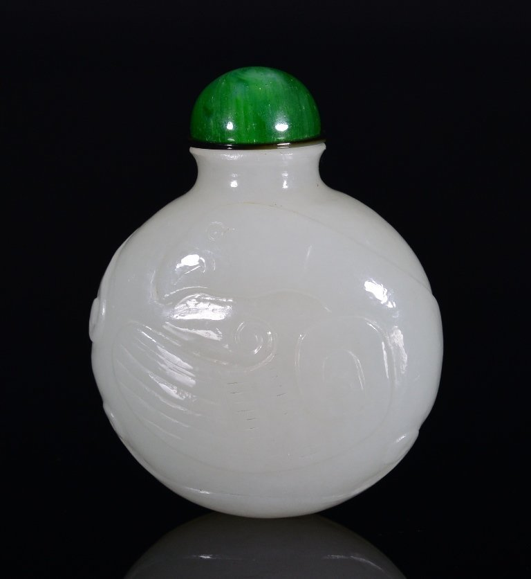 A CARVED WHITE JADE SNUFF BOTTLE