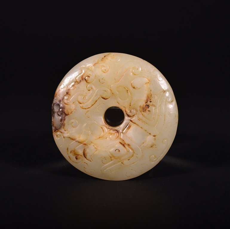 A CARVED WHITE AND RUSSET JADE PENDANT