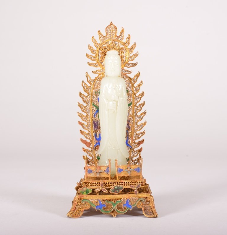 A WHITE JADE CARVING OF GUANYIN AND STAND
