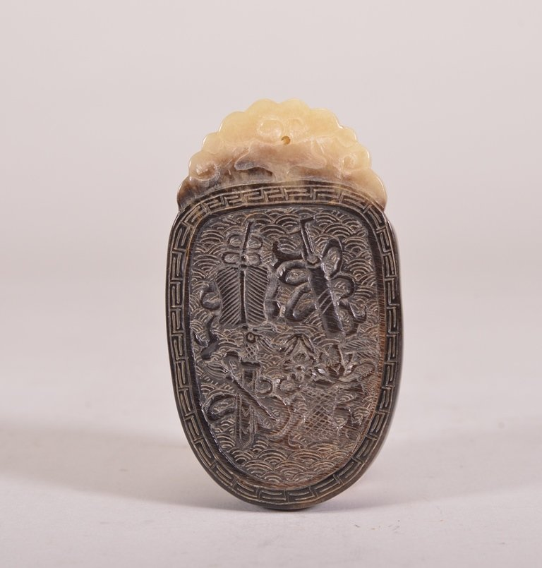 A CARVED HORN PENDANT