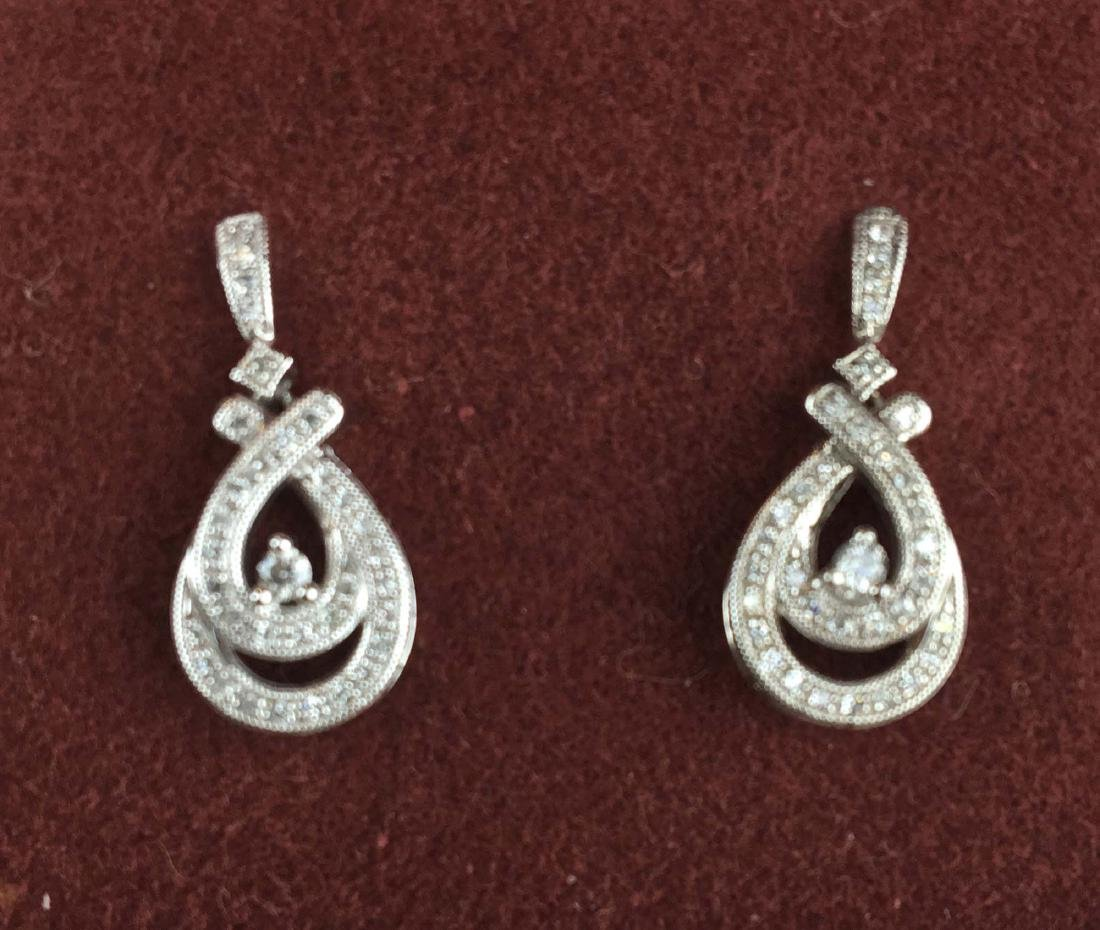 Pair of white gold and diamond oval drop earrings.