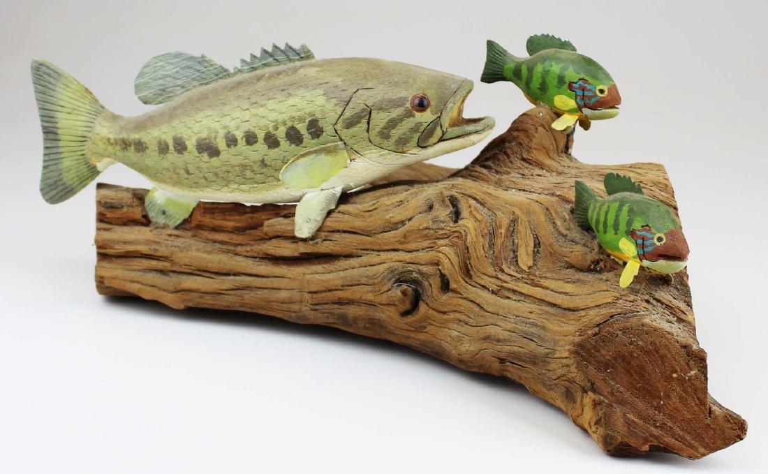 Rupert King Jr carving of bass chasing sunfish.