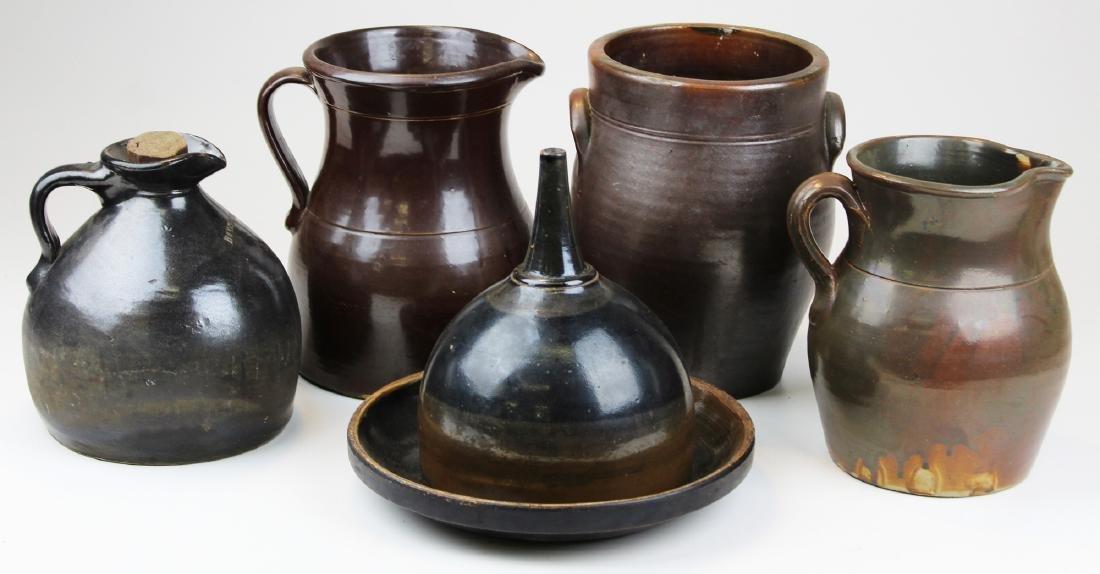six stoneware pieces with Albany slip glaze