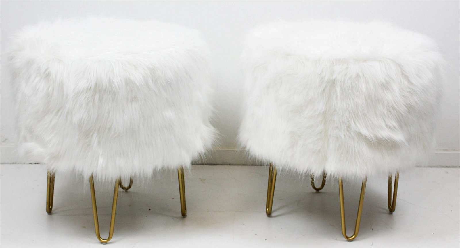 A pair of white fur round foot stools