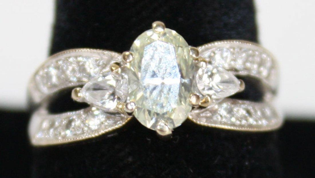 18k w.g. ladies diamond ring. Center oval cut diamond