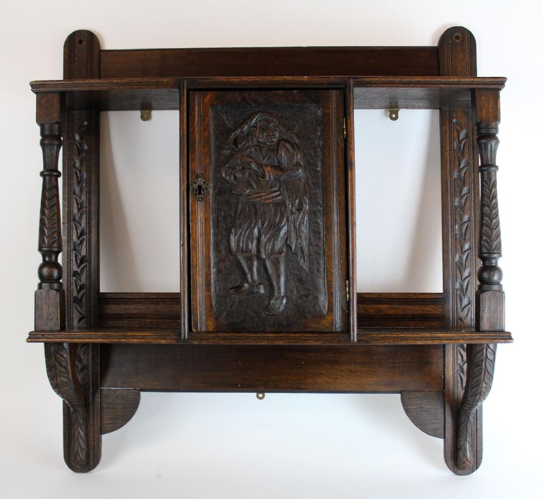 Carved figural wall shelf in oak