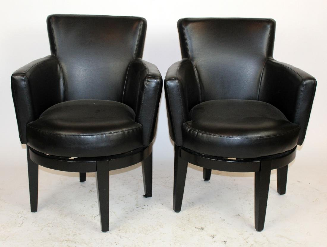 Pair of black leather swivel club chairs.