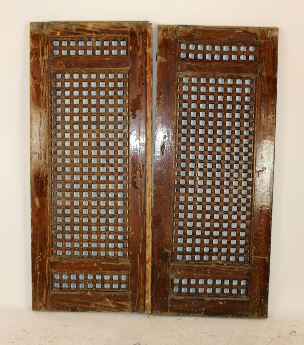 Pair of hand carved spindle wooden shutters