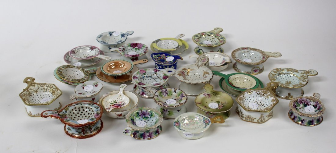 Collection of porcelain tea strainers and saucers