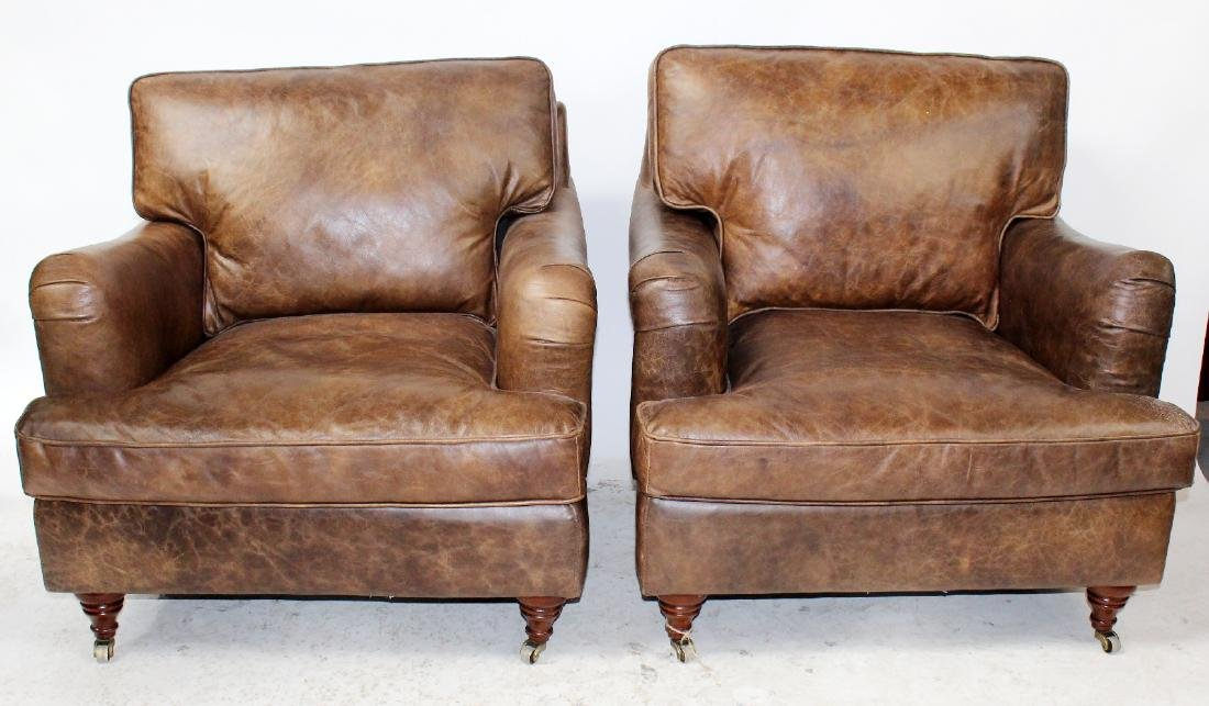 Pair of brown leather club chairs on legs