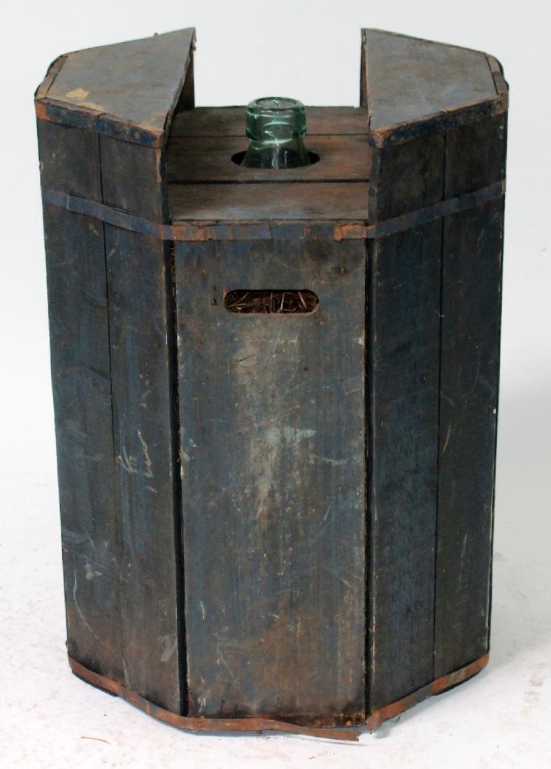 Glass demijohn bottle in wooden crate