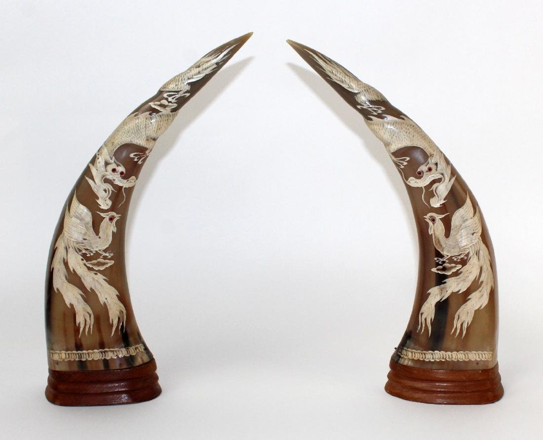 Pair of carved horn sculptures with dragons