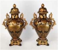 Pair of black and gold lidded ceramic urns