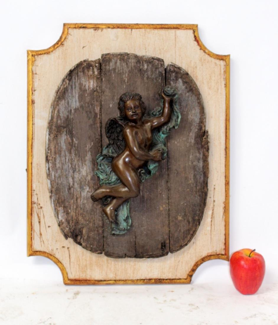 Bronze cherub plaque mounted on board
