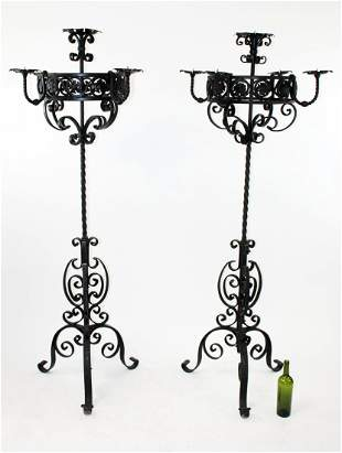 Pair of black iron scrolled candle torcheres