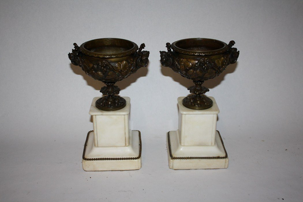 17: Pair of decorated bronze urns on marble bases