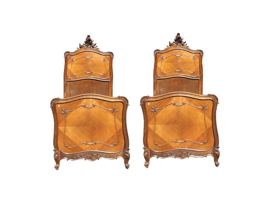 A pair of French Louis XV carved walnut twin beds