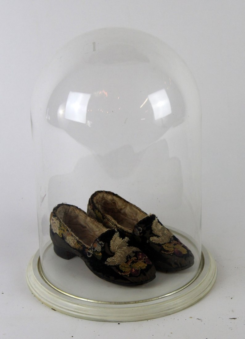 Victorian children's shoes under glass dome
