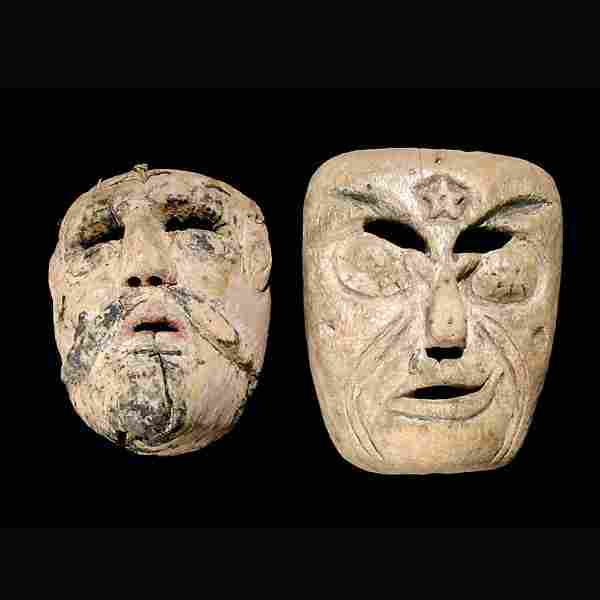 two mexican masks. wood with feathered surface
