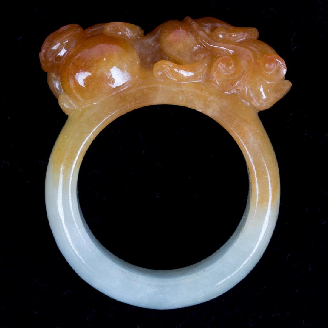 A Carved Celadon and Russet Jade Ring.