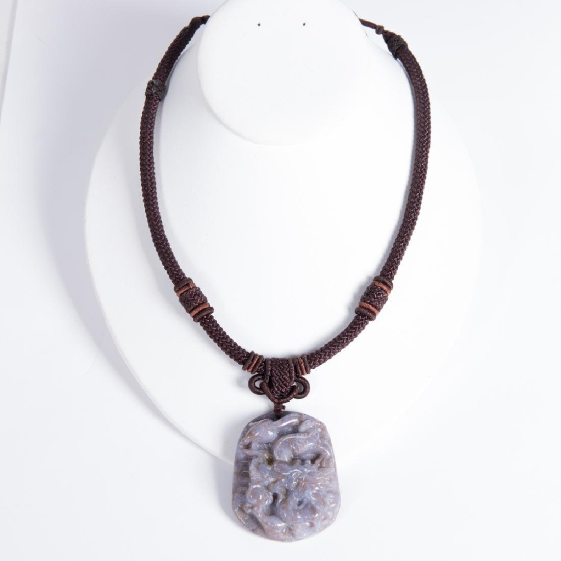 A Carved Lavender and Russet Jade Pendant on Rope