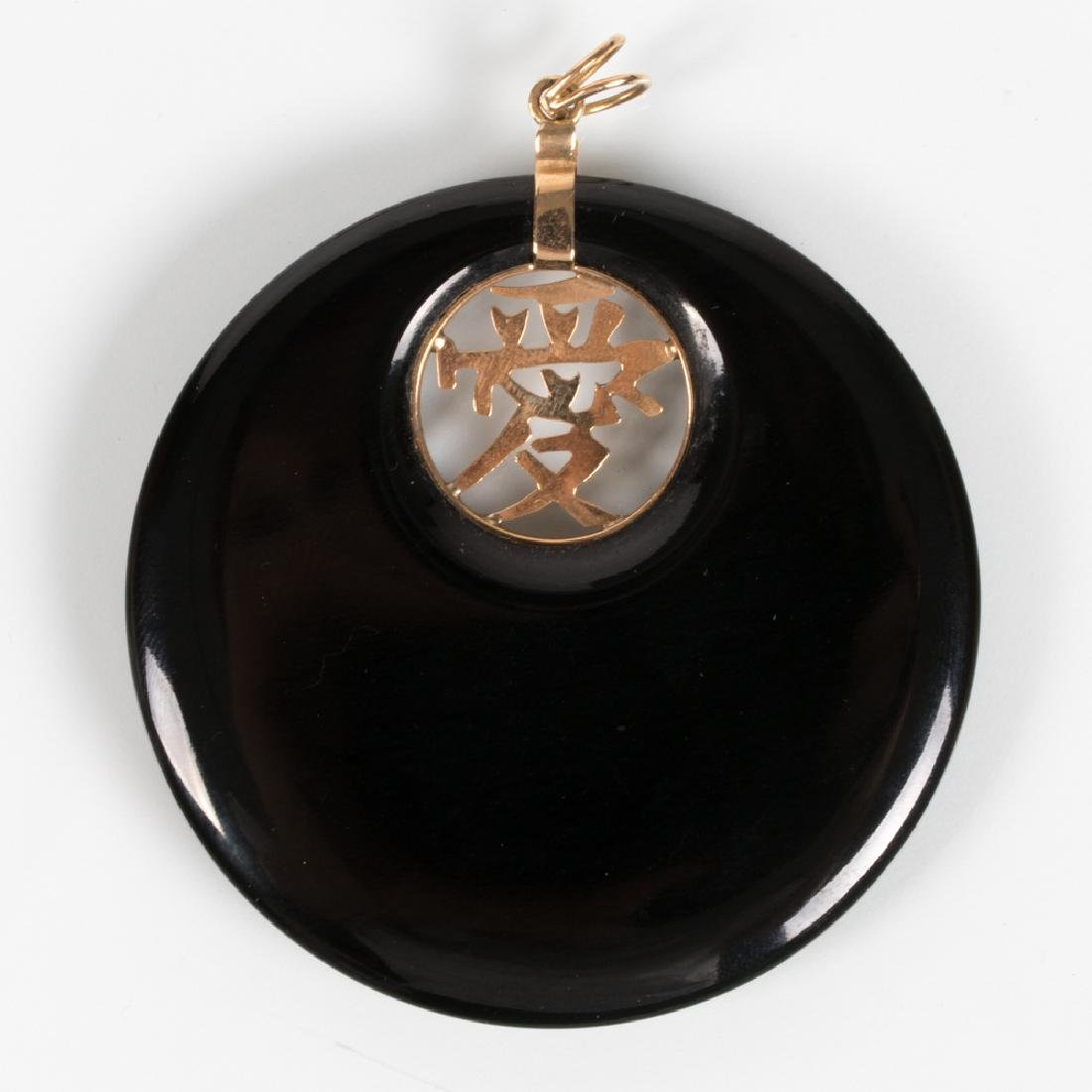 A 14kt. Yellow Gold and Carved Onyx Disk Pendant.