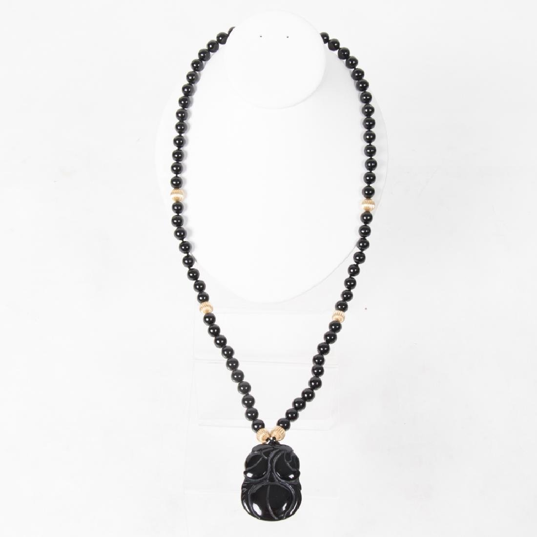 A Carved Obsidian Beaded Necklace,