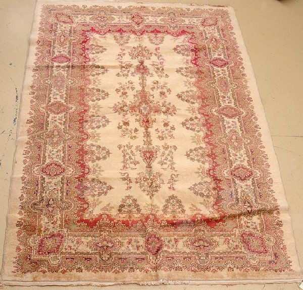 "An Antique Persian Kirman Wool Rug, 6' 9"" x 9' 9"""