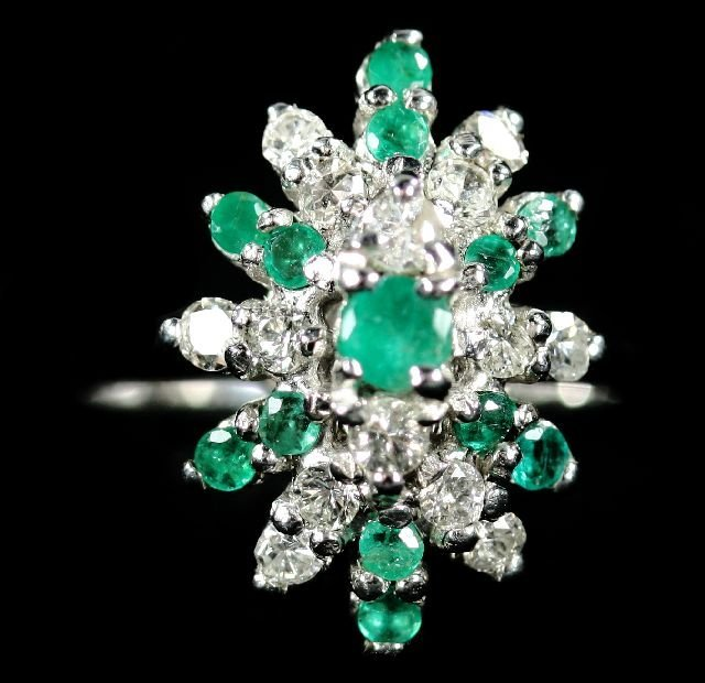 19: A 14kt. White Gold Diamond and Emerald Melee Ring.