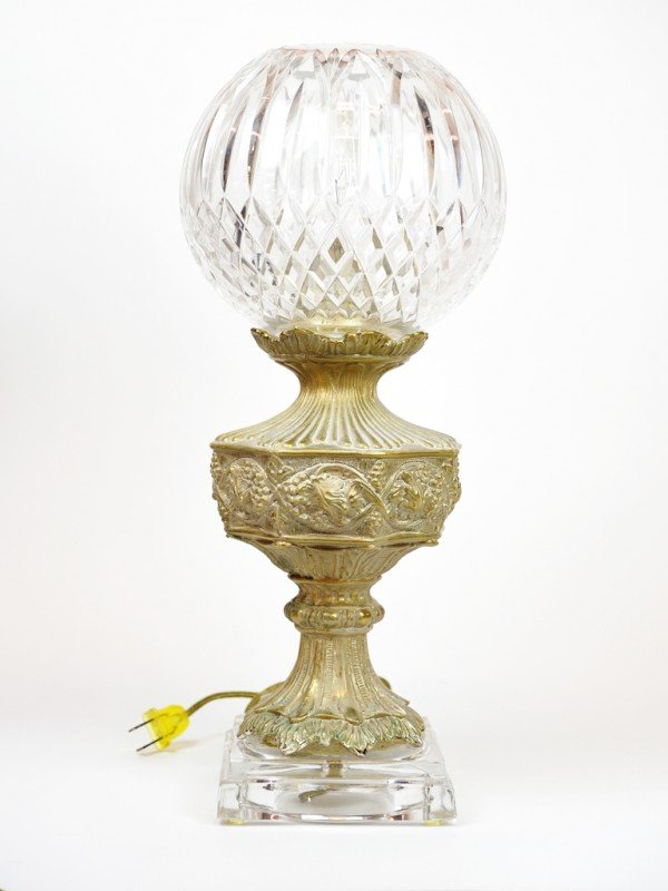 5: A SPHERICAL CUT CRYSTAL AND GILDED METAL LAMP ON A B