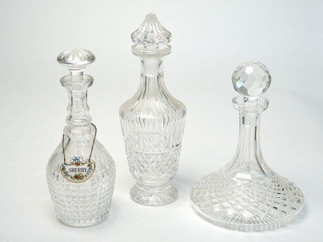 8: A GROUP OF THREE CUT GLASS ROUND DECANTERS